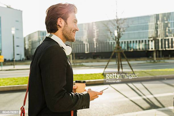 Germany, Frankfurt, Young businessman walking the city with cup of coffee, using mobile phone