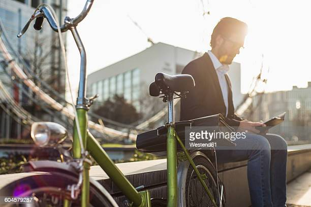 Germany, Frankfurt, Young businessman with bike, sitting on wall, taking a break