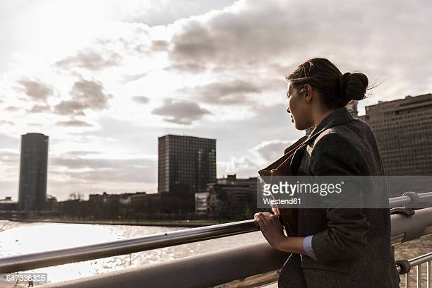 Germany, Frankfurt, Young woman looking at river