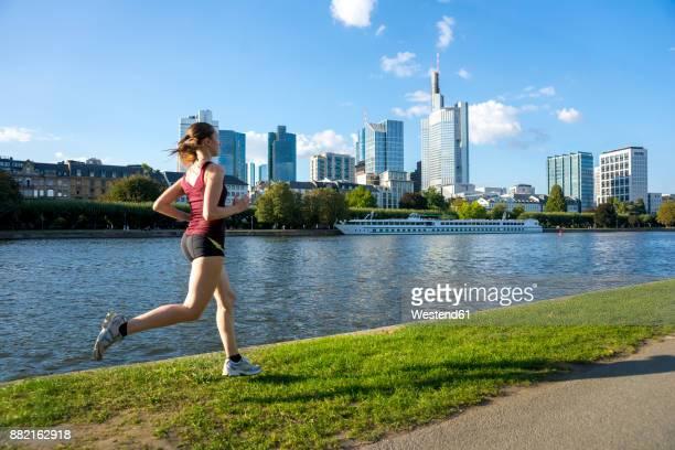 germany, frankfurt, young woman running at riverside - 川岸 ストックフォトと画像