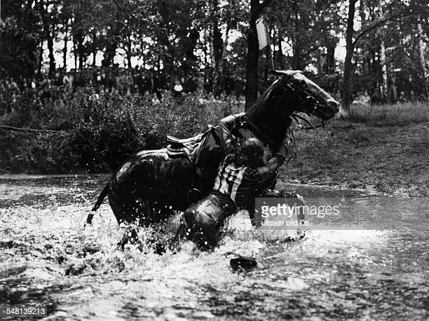 Germany Free State Prussia Berlin 1936 Summer Olympics Eventing Captain Raguse hanging on the neck of his horse during the crosscountry phase in...