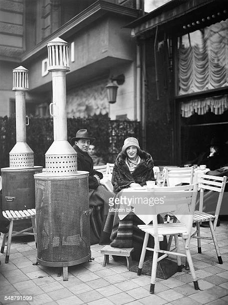 Germany Free State Prussia Berlin a man and a woman sitting on a terrace with patio heaters at a cafe at Kurfuerstendamm Photographer Badekow Vintage...
