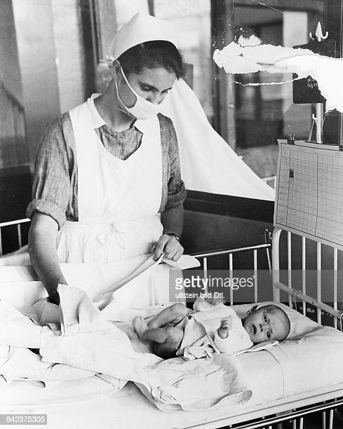 Germany Free State Prussia Berlin Brandenburg provincial women's clinic BerlinNeukoelln nurse with face mask changing a baby's diaper 1931...