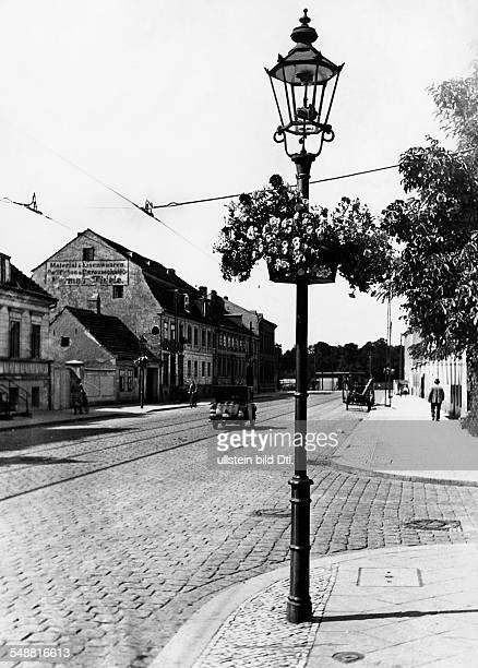 Germany Free State Prussia Brandenburg Province: Teltow: Street scene, in the foreground is a street light with flowers - 1932 - Photographer:...