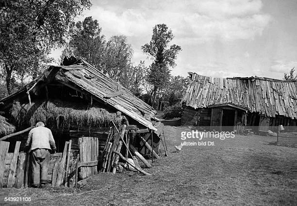 Germany Free State Prussia East Prussia Province Couronian Spit man in front of an old house which bogged down in the swamp region Bolschoje...