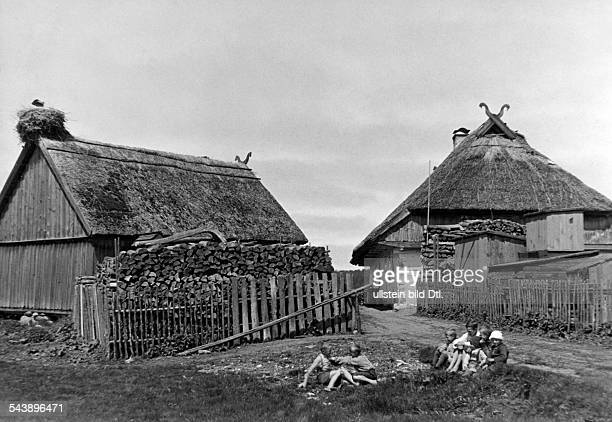 Germany Free State Prussia East Prussia Province Curonian Lagoon children playing behind a thatched farmhouse with a stork's nest 1934 Photographer...