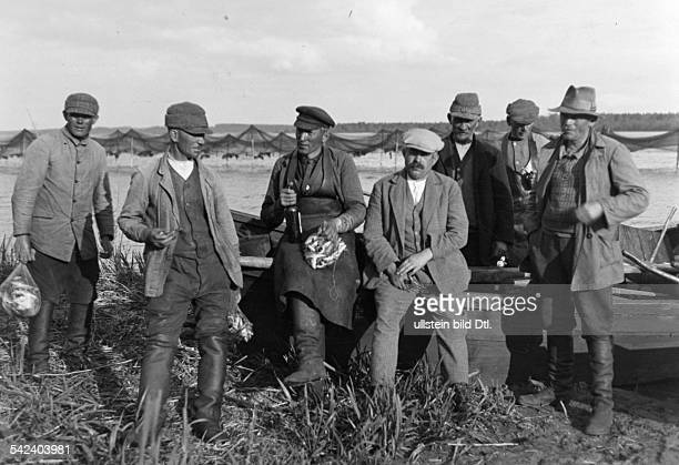 Germany Free State Prussia East Prussia Province Masuria farmers with nets full of small fish which they are allowed to keep after having worked the...