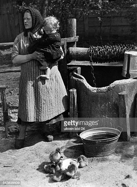 Germany Free State Prussia East Prussia Province Masuria Female farmer carrying a child in her arms at a well In the foreground drinking chicks 1933...
