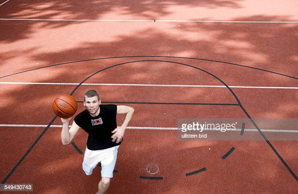 Germany: Free time.- A young man playing basketball.
