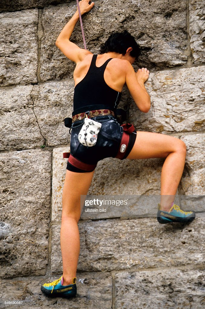 Free time.- A young woman climbing up a stone wall.