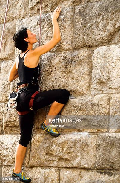 Free time A young woman climbing up a stone wall