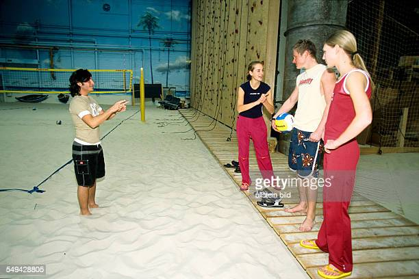 Free time Four youth doing sports in a beachvolleyball hall