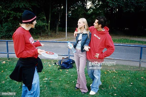 Free time Three youth in a park they are talking one of them is holding a frisbee