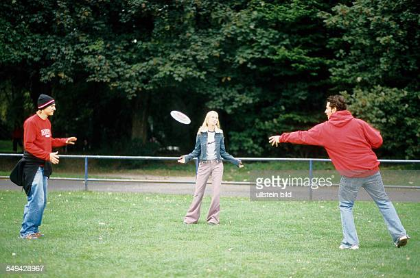 Free time Three youth meeting in a park they are playing frisbee