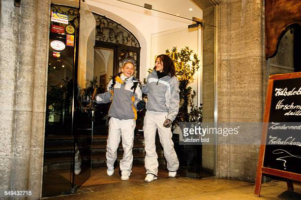 Germany: Free time.- Two friends in their skiing holiday; at the hotel entrance.