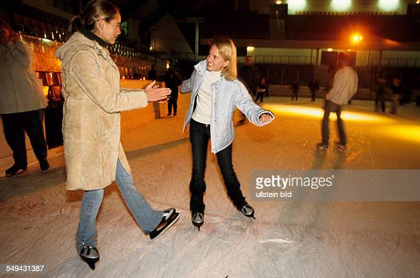 Germany: Free time.- Two young girls in an ice-skating rink; skating.