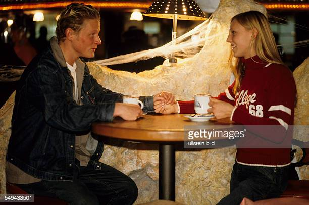 Free time Two young persons at a table their are holiding each others hand and drinking hot chocolate