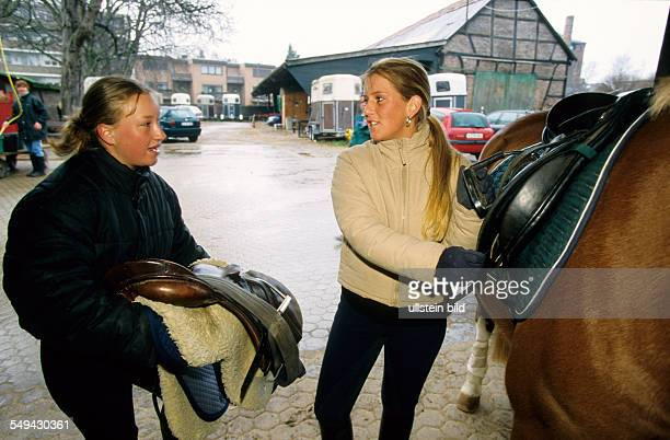 Free time Two young women on a stud farm they are saddling the horses
