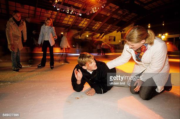 Germany: Free time.- While skating in an ice-skating rink; a boy falled and is lieing on the ice being injured.