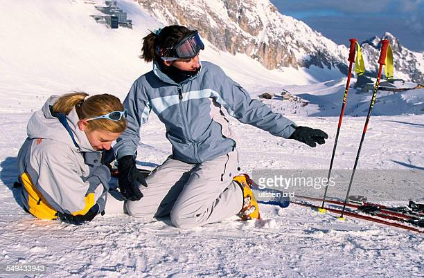 Germany: Free time.- Young persons skiing and snowboarding in the mountains; fall.