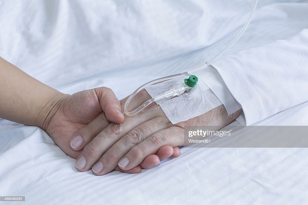 Germany, Freiburg, Woman holding hand of man in hospital, close up : Stockfoto