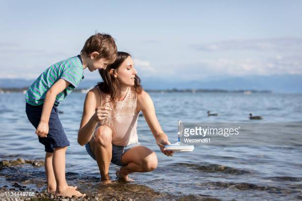 germany, friedrichshafen, lake constance, mother and son with toy boat at lakeshore - bodensee stock-fotos und bilder