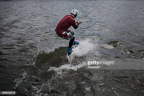germany, garbsen, wakeboarder at blue lake - man bending over from behind stock photos and pictures
