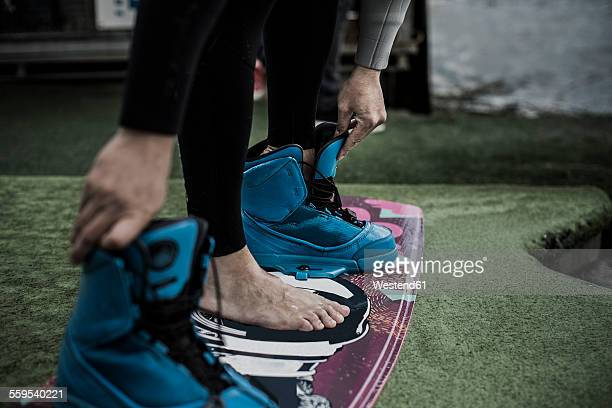 Germany, Garbsen, wakeboarder undressing shoes