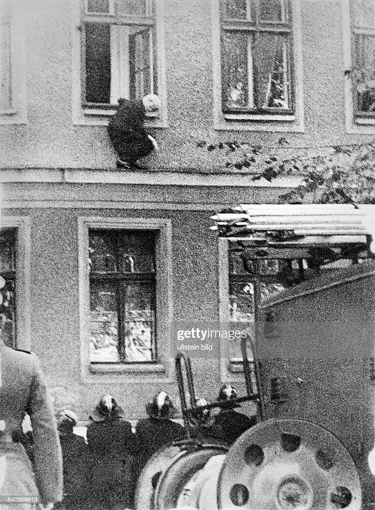 Germany / GDR, Berlin. The building of the wall. Frieda Schulze escaping out of the window of her flat in East-Berlin to West-Berlin. Bernauer Strasse, September 1961 : Foto jornalística
