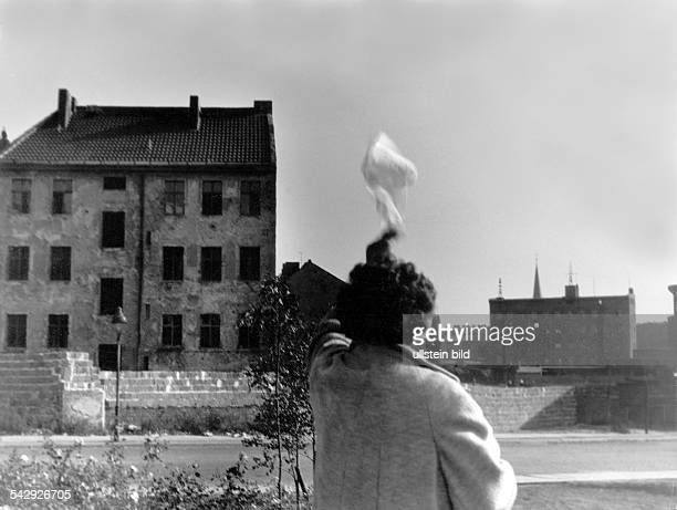 Germany / GDR Berlin The building of the wall Woman waving a kerchief at the wall Bernauer Strasse October 1961