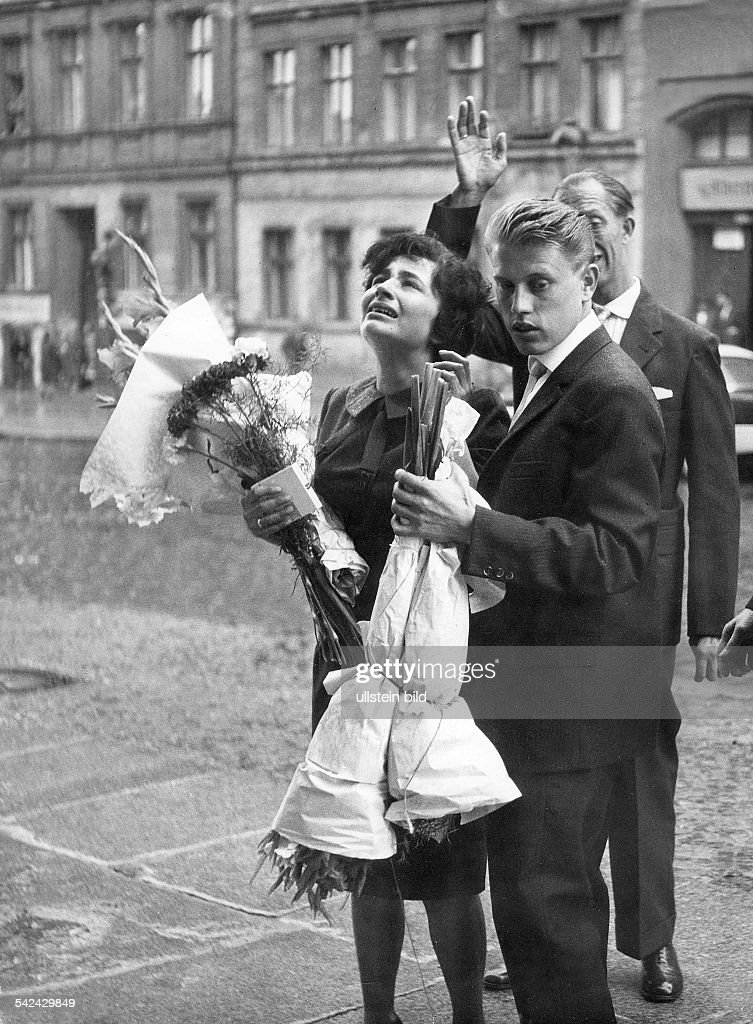 Germany / GDR, Berlin. Wedding scene at Bernauer Strasse. The wedding couple in West-Berlin standing at the border. They look to the window of the house of the parents of the bride, which is in East-Berlin. On picture no. 00338156 you will see the sc : News Photo