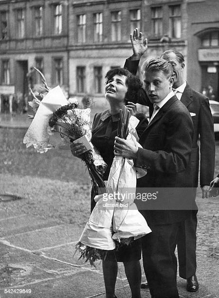 Germany / GDR Berlin Wedding scene at Bernauer Strasse The wedding couple in WestBerlin standing at the border They look to the window of the house...