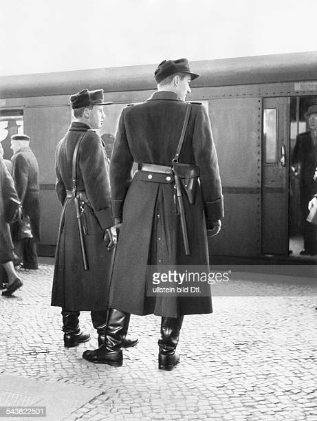 Germany GDR Volkspolizei Transport Police Two policemen observing visitors traffic to the 'Gruene Woche exhibition' at the SBahn station Witzleben