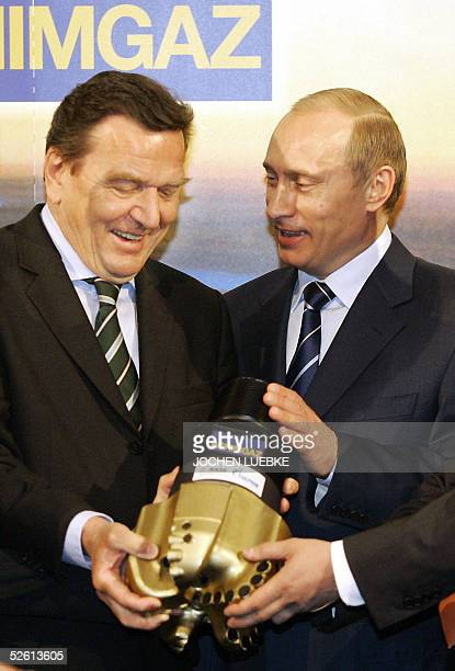 German Chancellor Gerhard Schroeder and Russian President Vladimir Putin present a drill head as they visit the Hanover Fair for industrial...