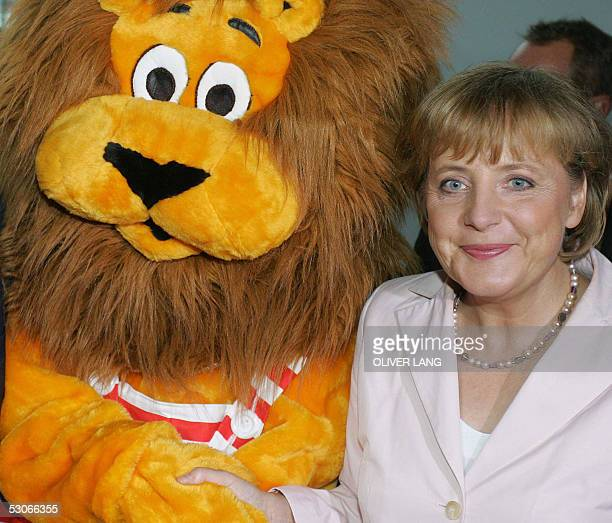 German opposition leader Angela Merkel shakes hands with a plush lion as she takes part in a summer party 14 June 2005 in Berlin Merkel leader of the...