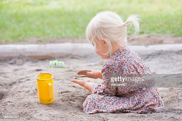 Germany, Girl playing with sand on playground