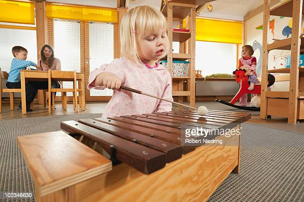 Germany, Girl (3-4) playing xylophone, Female nursery teacher with children in background, portrait