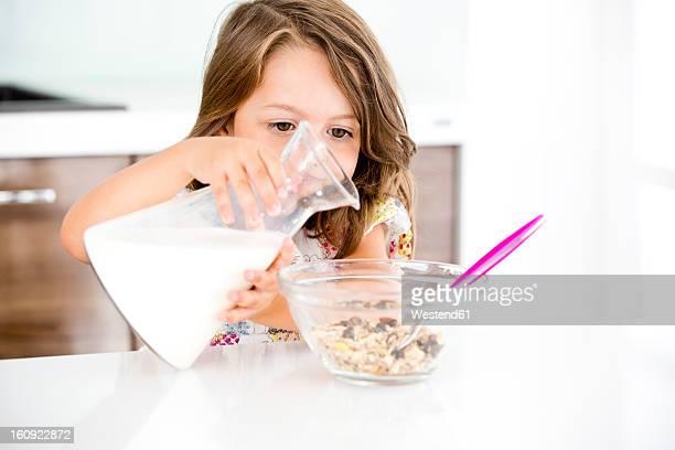 Germany, Girl pouring milk in muesli