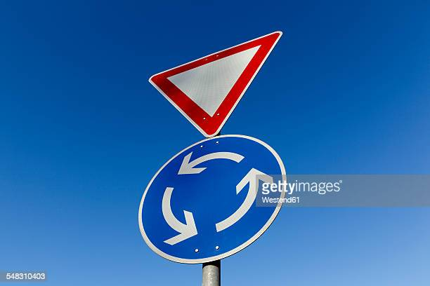 germany, give way and roundabout sign in front of blue sky - give way stock pictures, royalty-free photos & images