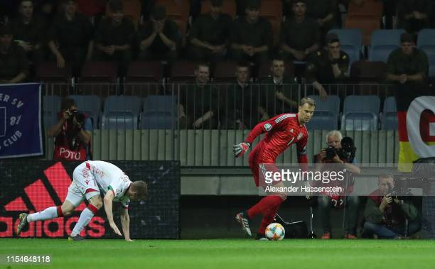 Germany goalkeeper Manuel Neuer controls the ball as Yuri Kovalev of Belarus stumbles during the UEFA Euro 2020 qualifier match between Belarus and...