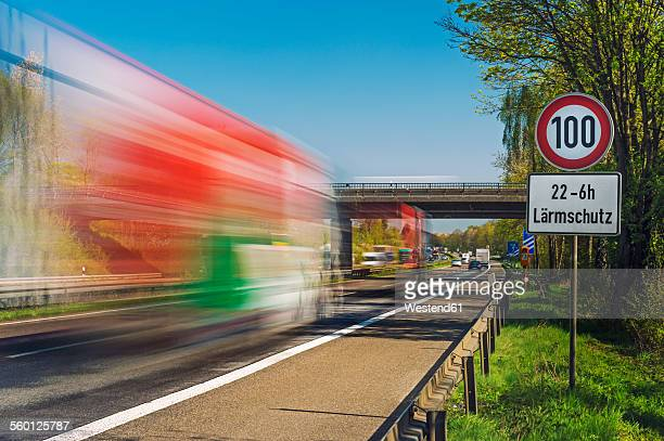 Germany, Grevenbroich, trucks on motorway, sign speed limit, noise protection