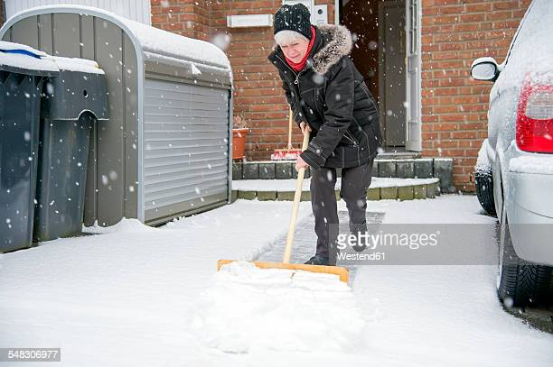 germany, grevenbroich, woman shoveling snow in front of house - snow shovel stock photos and pictures