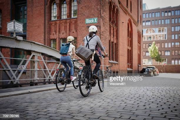 Germany, Hamburg, back view of couple riding electric bicycles at Old Warehouse District