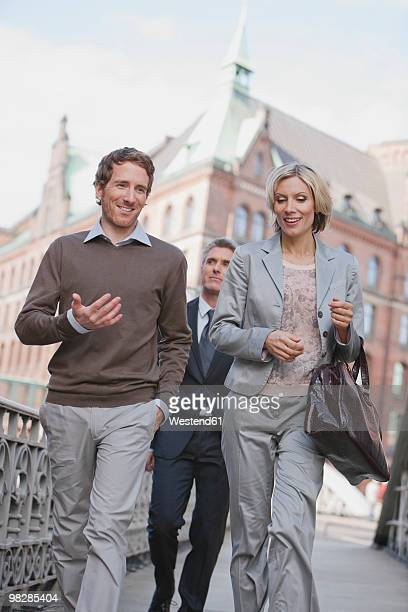Germany, Hamburg, Business people walking on street, smiling