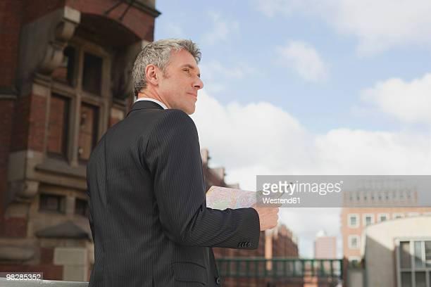 Germany, Hamburg, Businessman holding street map, looking away