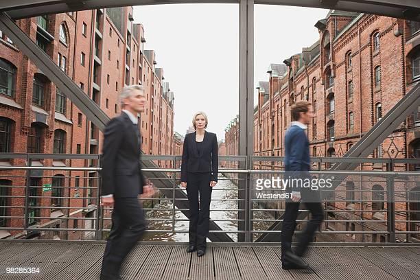 Germany, Hamburg, Businessmen crossing bridge, businesswoman in background