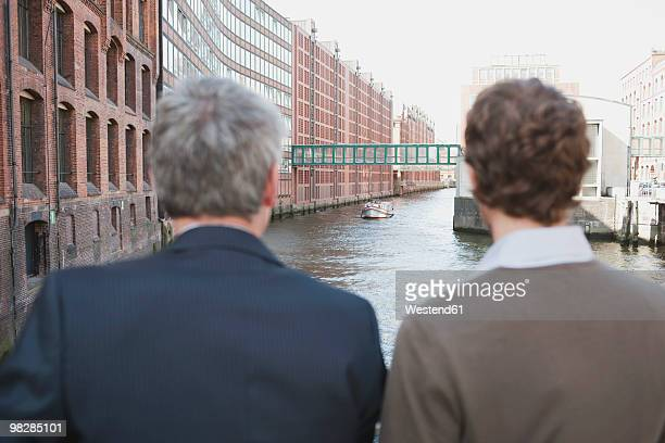Germany, Hamburg, Businessmen looking at canal, rear view