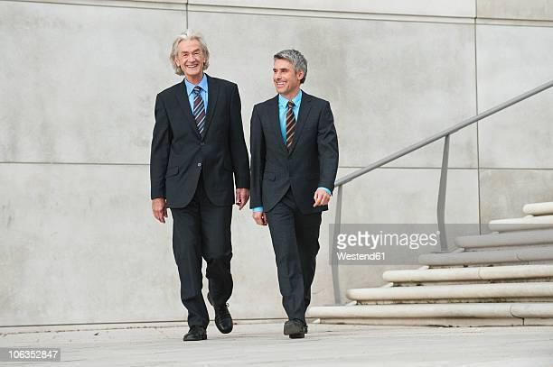 Germany, Hamburg, Businessmen walking together, smiling