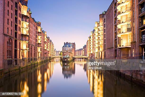 Germany, Hamburg, canal in Speicherstadt District, warehouses illuminated at dusk