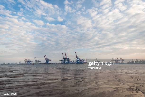 germany, hamburg, clouds over elbe river with harbor cranes in background - エルベ川 ストックフォトと画像